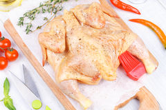 Fresh raw chicken prepared for roast with thyme and tomatoes Stock Photography