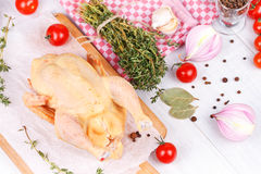 Fresh raw chicken prepared for roast with thyme and tomatoes. Cherry Royalty Free Stock Photos