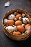 Fresh raw chicken and quail eggs in sieve. Selective focus Royalty Free Stock Images
