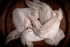 Fresh raw chicken wing. Fresh raw chicken wings on a cutting board on rustic table Royalty Free Stock Photography