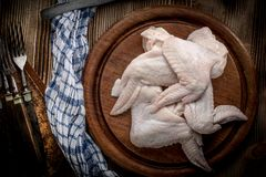 Fresh raw chicken wing. Fresh raw chicken wings on a cutting board on rustic table Stock Photos