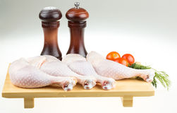 Fresh raw chicken wings on chopping. Board with roma tomatoes Stock Photo