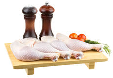 Fresh raw chicken wings on chopping board. With roma tomatoes Stock Photography