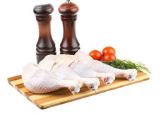 Fresh raw chicken wings. On chopping board with roma tomatoes Royalty Free Stock Photography