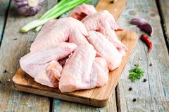 Fresh raw chicken wings with garlic, onion and peppers on a cutting board. Fresh raw chicken wings with garlic and peppers on a cutting board on rustic table Royalty Free Stock Photo