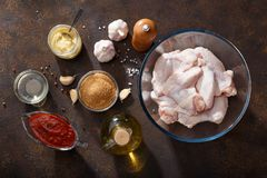 Fresh raw chicken wings and ingredients for bbq sauce on brown rusty background. Top view Stock Photos