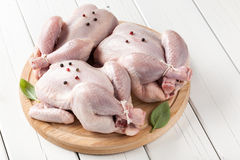 Fresh raw chickens on cutting board. Three small raw chickens on cutting board stock image