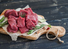 Fresh raw chopped beef, spices and herbs on an olive board. On a  wooden background Royalty Free Stock Images