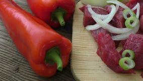 Fresh raw chopped beef on a wooden cutting board with fresh organic vegetables, onion, garlic. stock footage