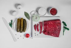 Fresh raw chopped beef on a wooden cutting board with spices, herbs and vegetables. White colored Stock Photo