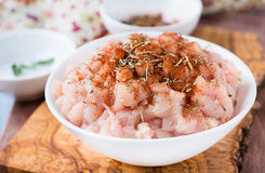Fresh raw chopped chicken meat in a bowl. Fresh raw chopped chicken meat with seasoning in a bowl, closeup, selective focus Royalty Free Stock Images