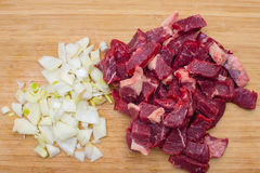 Fresh raw chopped meat beef and chopped white onion on an wooden cutting board. Stock Photography