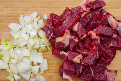 Fresh raw chopped meat beef and chopped white onion on an wooden cutting board. Selective focus Royalty Free Stock Photos