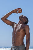 Fresh raw coconut water. Shirtless lean African American man pours water from fresh coconut into mouth to quench thirst outside on beach while coconut water runs Stock Photo