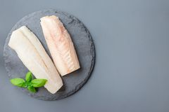 Fresh raw cod fillet with basil on stone plate, horizontal, copy stock image