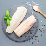 Fresh raw cod fillet with spices, pepper, salt, basil on a stone royalty free stock image