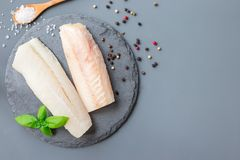 Fresh raw cod fillet with spices, pepper, salt, basil on stone p. Fresh raw cod fillet with spices, pepper, salt, basil on a stone plate, horizontal, copy space royalty free stock images