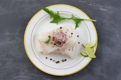 Fresh raw cod fish fillet on a plate with parsley and lemon  on grey slate background. Fresh raw cod fish fillet on a plate with parsley and lemon  against grey Stock Photos