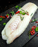 Fresh Raw Cod loin fillet with rosemary, chillies, cracked pepper and lemon on stone board.  Royalty Free Stock Photography