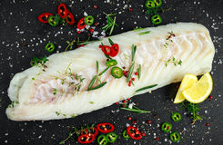 Fresh Raw Cod loin fillet with rosemary, chillies, cracked pepper and lemon on stone board.  Royalty Free Stock Image