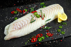 Fresh Raw Cod loin fillet with rosemary, chillies, cracked pepper and lemon on stone board.  Royalty Free Stock Photo
