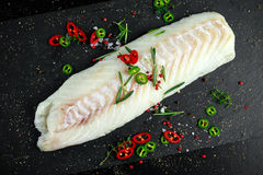 Fresh Raw Cod loin fillet with rosemary, chillies, cracked pepper on stone board.  Royalty Free Stock Photos