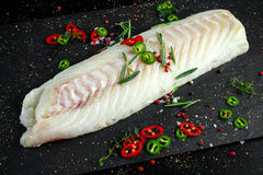 Fresh Raw Cod loin fillet with rosemary, chillies, cracked pepper on stone board.  Royalty Free Stock Photo