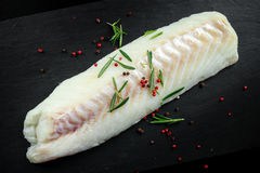 Fresh Raw Cod loin fillet with rosemary, cracked pepper on stone board.  Royalty Free Stock Photo