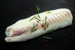 Fresh Raw Cod loin fillet with rosemary, cracked pepper on stone board Royalty Free Stock Image