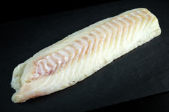 Fresh Raw Cod loin fillet on stone board Stock Image