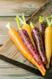 Fresh raw colorful carrots roots. Purple, yellow and orange on old wooden table. Healthy food vegetable background with copy space Stock Images