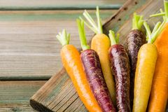 Fresh raw colorful carrots roots. Purple, yellow and orange on old wooden table. Healthy food vegetable background with copy space Royalty Free Stock Photography