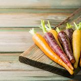 Fresh raw colorful carrots roots. Purple, yellow and orange on old wooden table. Healthy food vegetable background with copy space Stock Image
