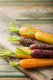 Fresh raw colorful carrots roots. Purple, yellow and orange on old wooden table. Healthy food vegetable background with copy space Stock Photos