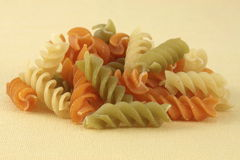 Fresh raw and colorful fusilli. Beautiful and fresh raw fusilli ,thick, corkscrew shaped pasta on fine linen Royalty Free Stock Photography