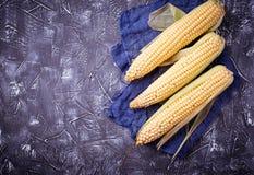 Fresh raw corn on concrete table. Selective focus Stock Photo
