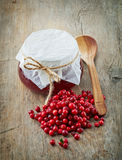 Fresh raw cowberries and jar of jam. On old wooden table Royalty Free Stock Image