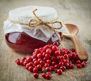 Fresh raw cowberries and jar of jam. On old wooden table Royalty Free Stock Photo