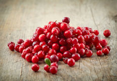 Fresh raw cowberries. On old wooden table Stock Photography