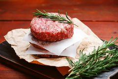 Fresh raw cutlets for burger from beef. wooden background, rustic style. Fresh raw cutlets for burger from beef. wooden background, rustic style Royalty Free Stock Photos