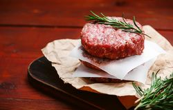 Fresh raw cutlets for burger from beef. wooden background, rustic style.  Royalty Free Stock Photos