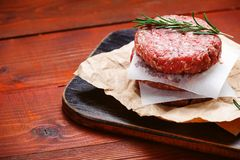 Fresh raw cutlets for burger from beef. wooden background, rustic style.  Royalty Free Stock Photography
