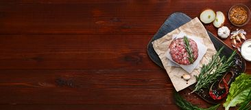Fresh raw cutlets for burger from beef. wooden background, rustic style.  Royalty Free Stock Images