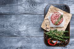 Fresh raw cutlets for burger from beef. wooden background, rustic style.  Royalty Free Stock Photo