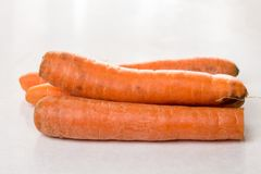 Fresh raw dirty carrot from the garden on the white marble background.  Royalty Free Stock Images