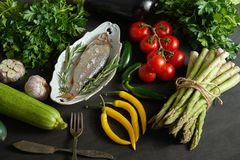Fresh raw dorada fish in a white dish with a set of vegetables on a black table. One fresh raw dorada fish in a white dish with a set of vegetables on a black stock photography