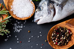 Fresh raw dorado fish with spices and herbs on black background, top view. Delicious portion of fresh fisht with aromatic herbs, spices and vegetables - healthy Stock Images