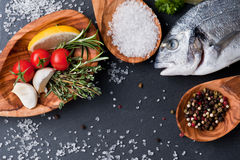 Fresh raw dorado fish with spices and herbs on black background, top view. Delicious portion of fresh fisht with aromatic herbs, spices and vegetables - healthy Stock Photos