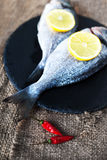 Fresh raw Dorado sea fish on wooden table  with lemon and red ch. Fresh raw  sea fish on wooden table  with lemon and red chilli pepper. Top view Royalty Free Stock Images