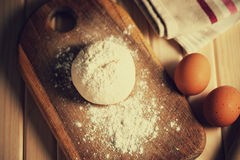 Fresh raw dough. Eggs and tablecloth on a table Royalty Free Stock Photos